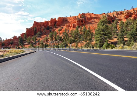 Vibrant colors of red sandstone delight travelers along the highway to Bryce National Park when they pass through scenic Red Canyon - stock photo