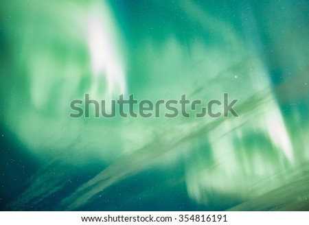 Vibrant colors of the northern lights (Aurora Borealis) dancing in the night sky in Finland. Abstract nature background with green tones. - stock photo
