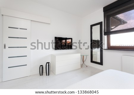 Vibrant cottage - white commode and black tv in bedroom - stock photo