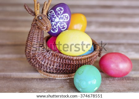 vibrant Easter Eggs in a wicker deer basket on a wooden background - stock photo