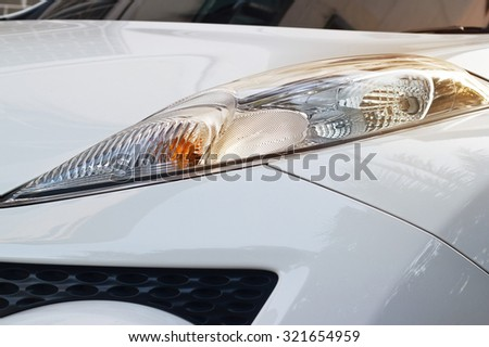 vibrant headlights of white car in the sunset on street - stock photo
