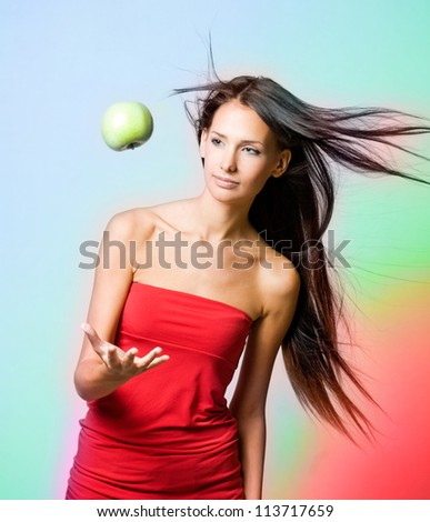 Vibrant health girl with levitating apple on rainbow background. - stock photo