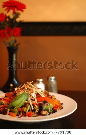 Vibrant, healthy salad at a table set in a minimalistic Spanish style; plenty of colorful space for copy