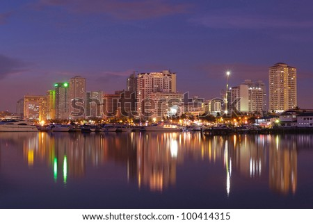 Vibrant Manila bay Philippines city night-scape and buildings reflection.