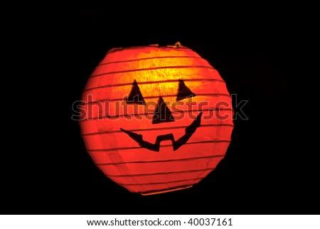 Vibrant orange and red Halloween lamp in the dark - stock photo