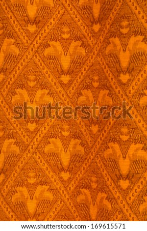 Vibrant orange curtain fabric, with fleur-de-lys pattern, possible background use. - stock photo