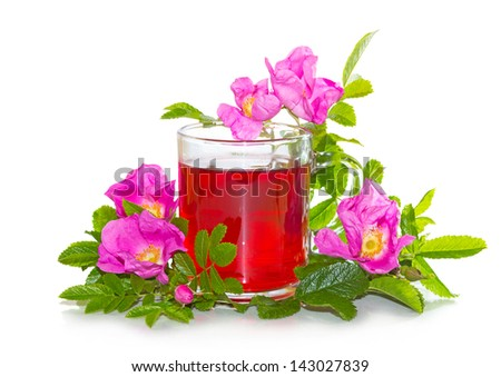 Vibrant pink Rosa canina flowers, or dog rose, with a red herbal infusion or tea in a clear glass mug prepared from the hips of the plant which are rich in antioxidants and vitamin c - stock photo