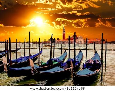 Vibrant sunrise over the lagoon of Venice, Italy with gondolas - stock photo