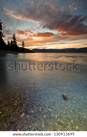 Vibrant Sunset from shore of Mountain lake - stock photo