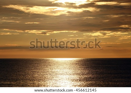 Vibrant Sunset In The Front Sun Light Over Black Atlantic Ocean Calm Water Surface And Orange Sky, Panoramic View - stock photo