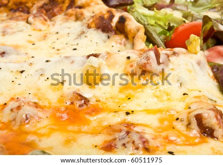 Vibrant tasty looking home made pizza and salad with dressing. - stock photo
