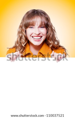Vibrant young woman laughing merrily while holding a blank white sign for your advertising and text on a colourful orange studio background with gradient - stock photo