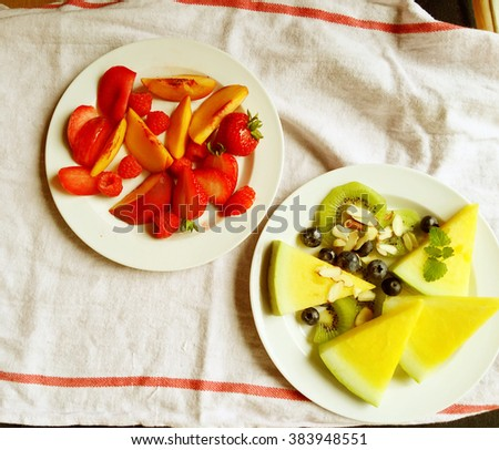 Vibrantly-colored fresh watermelon, kiwifruit, strawberries, peaches, raspberries, blueberries and almonds with a dish towel - stock photo