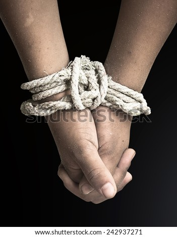 Victim boy with hands tied up with rope in emotional stress and pain, afraid, restricted, trapped, call for help, struggle, terrified. - stock photo