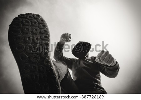 Victim's pov perspective, attacked on the street, being punched and mugged by aggressive violent man in hooded jacket, monochromatic black and white image. - stock photo