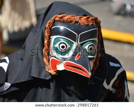 VICTORIA BC CANADA JUNE 24 2015: Native Indian man in traditional costume and wooden mask. First Nations in BC constitute a large number of First Nations governments and peoples in the province of BC - stock photo