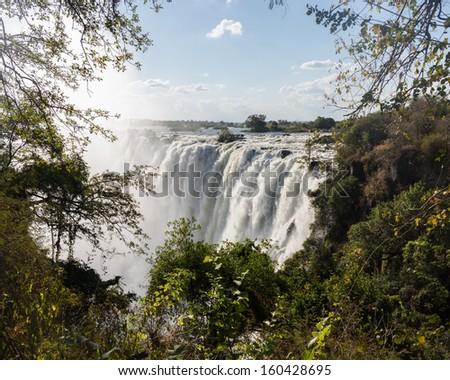 Victoria Falls (or Mosi-oa-Tunya - the Smoke that Thunders) waterfall in southern Africa on the Zambezi River at the border of Zambia and Zimbabwe. Image taken from Zambian side of falls - stock photo
