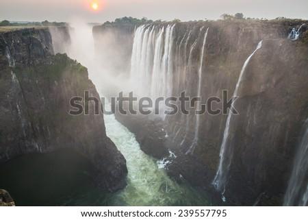 Victoria Falls sunset with zambezi river and red sun, View from Zambia - stock photo