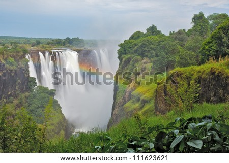 Victoria Falls, Zimbabwe, with bright rainbow - stock photo