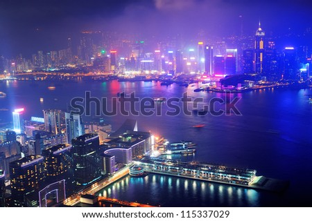 Victoria Harbor aerial view with Hong Kong skyline and urban skyscrapers at night. - stock photo