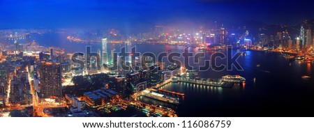 Victoria Harbor aerial view with Hong Kong skyline and urban skyscrapers at night.