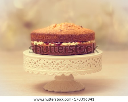 Victoria sponge cake filled with jam and buttercream - antique vintage tone effect added - stock photo