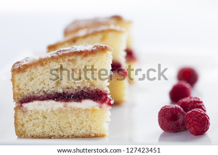 Victoria sponge cake with cream and jam filling, served with raspberries - stock photo