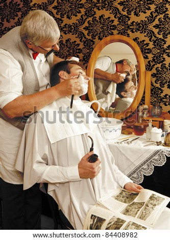 Victorian barber shaving a customer (the antique magazine is from 1910). - stock photo