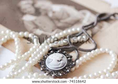 victorian cameo and pearl necklace in front of vintage picture - stock photo
