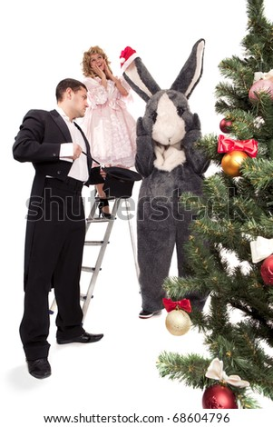 Victorian couple with funny grey rabbit stand  near a Christmas tree with gift boxes. Isolated over white background - stock photo