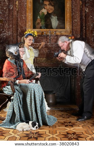 Victorian gentleman taking a photograph of his family with an antique camera (shot in Castle Den Brandt in Antwerp, Belgium, with signed property release for the castle interiors) - stock photo