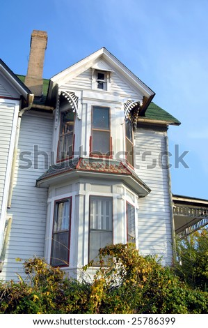 Victorian home with bay windows.  Unusual shingles have metal plates. - stock photo