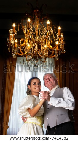 Victorian scene of two people dancing in a castle, under an antique chandelier. Shot in Castle Den Brandt in Antwerp, Belgium (with signed property release for the castle interiors). - stock photo