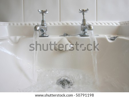 Victorian-style bathroom taps with running water - stock photo