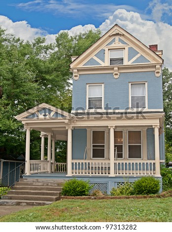 Victorian style brick home painted blue with cream trim after a rain in springtime.