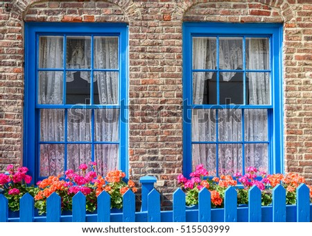 Victorian terraced brick town cottage front with garden flowers.