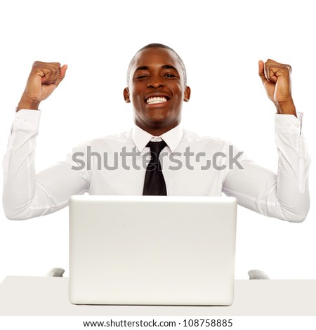 Victorious african business executive raising his hands in excitement sitting in front of laptop