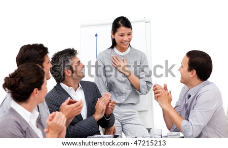 Victorious businesswoman applauded for her presentation against a white background - stock photo