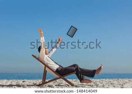 Victorious young businessman relaxing on his deck chair throwing his tablet away - stock photo