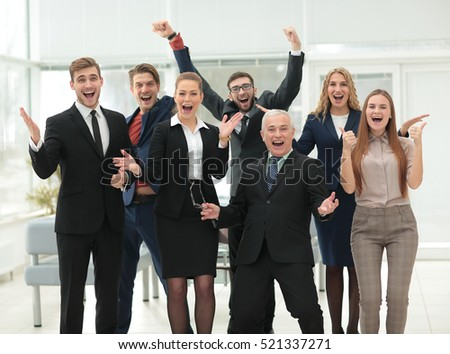 Victory in business. Happy businessman and business team on offi