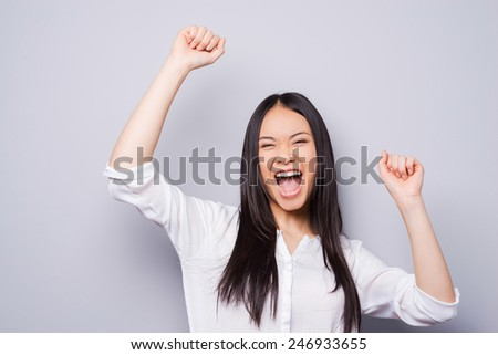 Victory is my second name! Portrait of a beautiful young woman keeping her arms raised standing against grey background  - stock photo