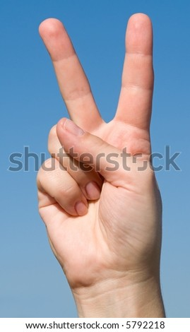 Victory sign with blue sky behind - stock photo