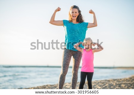 Victory... We both won the race along the water. We are like superheroes. A happy mother and daughter celebrate their victorious run along the beach at dusk, flexing their arms to show their strength. - stock photo
