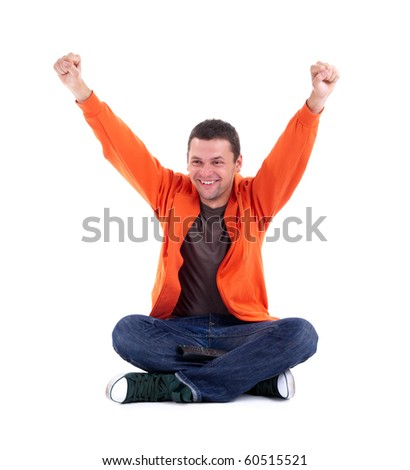 victory - young man in orange sweatshirt sitting on the floor with crossed legs and raised arms - stock photo