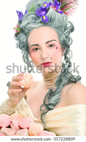 Victotian lady. Young woman in eighteenth century image posing with sweets - stock photo