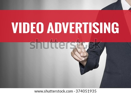 Video Advertising word on virtual screen push by business woman red tab - stock photo