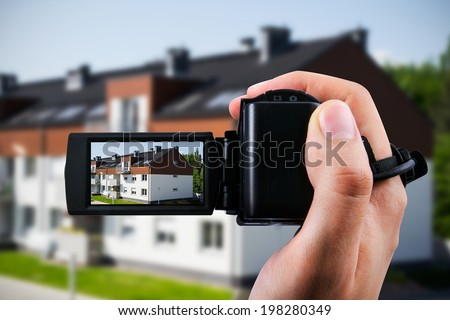 Video camera or camcorder recording new house - stock photo