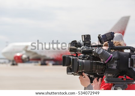 video cameras press and media working on public news event at airport