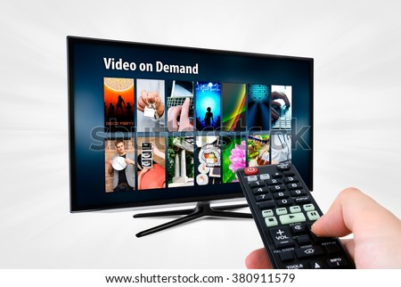 Video on demand VOD service on smart TV. Remote control in hand. - stock photo