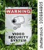 video security system warning signboard on a fence hedge - stock photo